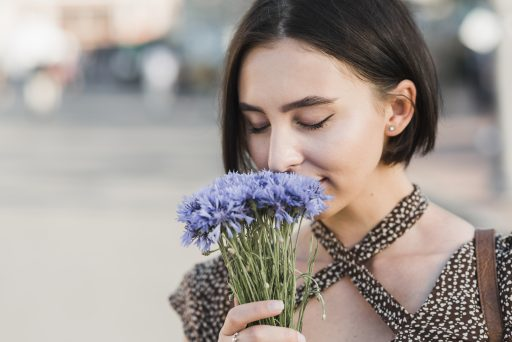 mujer oliendo flores concentrada