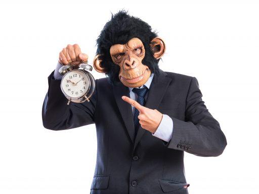 Hombre negocios con cara de mono y reloj en mano